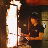 カウンター前で豪快に焼き上げる自慢の逸品【霧島鶏の炭火焼】