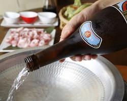 芋焼酎四合瓶を豪快に鍋の中へ 芋の香が部屋いっぱいに漂います