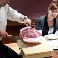 スタッフがお席でお肉を 手切りするパフォーマンスも人気