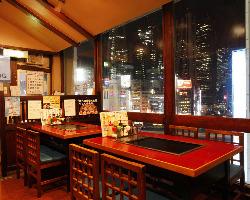 新宿のビルの輝きが眩しい、夜景とお好み焼きのコラボレーション