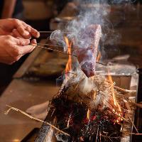 当店名物、束にした藁に火を付けて素材を豪快に炙る藁焼き料理