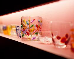 ピンクの壁にマッチした、ベネチアグラスのコレクションが並ぶ。