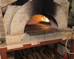 耐火性に優れ、遠赤外線効果もある大谷石で造った自慢のピザ釜