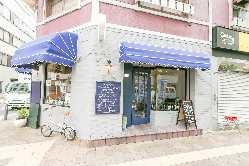 薄いグレーの壁に映える、青いテントの屋根が目印のお店です。