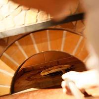 専任のスタッフが専門の石釜を使い焼き上げるピッツァ