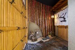 蹲踞と、梅が描かれた暖簾が印象的な玄関前。