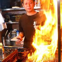 豪快な火柱を上げて焼き上げる「さつま知覧鶏の炙り焼き」