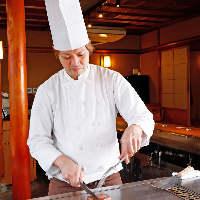 熟練のシェフが目の前の鉄板でステーキを焼き上げます