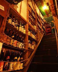 2階へ上がる階段の棚には、 100種以上の焼酎がずらり!