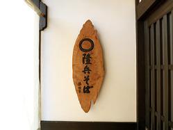 暖簾の向こうに存在感を示す木製の看板