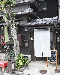 狭い間口の京町家ならではの佇まい。白い暖簾が目印です。