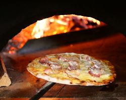 薪釜で焼き上げる自家製ピザ。火加減に気を付けながら焼いてます