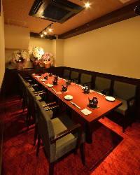 赤絨毯に白壁。くつろげる肘置きのある椅子席大人雰囲気の店内