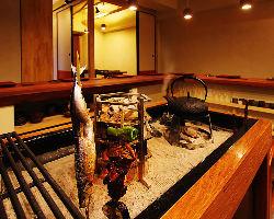 カウンターから望む 囲炉裏では旬の食材を調理